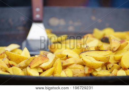 In a large frying pan prepares a large portion of fried potatoes.
