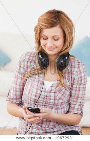 Mujer rubia con auriculares y reproductor de Mp3
