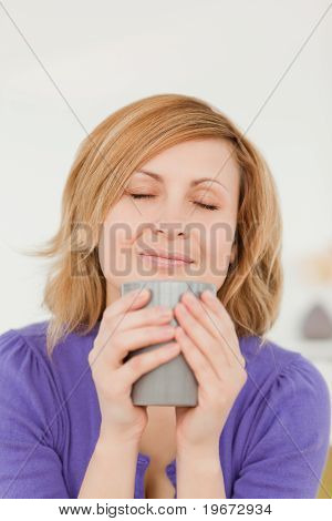 Attractive Red-haired Woman Holding And Smelling A Cup Of Coffee While Sitting On A Sofa