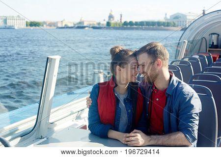 Amorous couple enjoying time on motor-boat