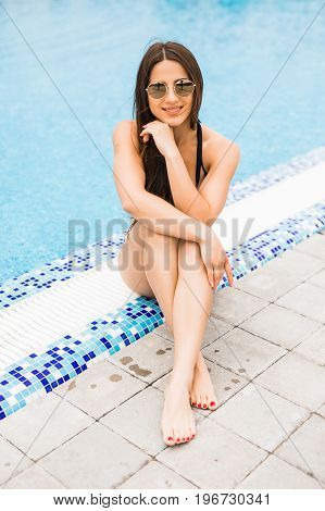 Beautiful Young Woman Sitting On Edge Of Swimming Pool. Summer Vocation