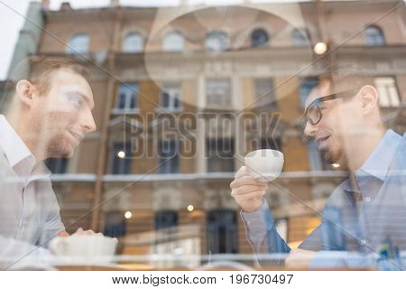 Two modern bankers having talk by tea in cafe