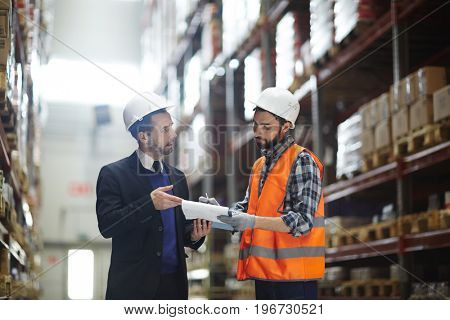 Portrait of warehouse manager wearing business suit talking to loader showing order list in aisle between tall shelves with packed goods