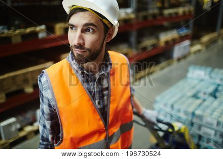 Portrait of bearded loader working in warehouse, pulling moving cart with retail goods in aisle between tall shelves