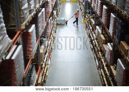 Side view of warehouse worker pulling moving cart between tall shelves with packed boxes and goods