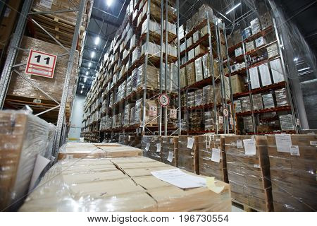 Large distribution warehouse with tall shelves and racks with packed goods in boxes