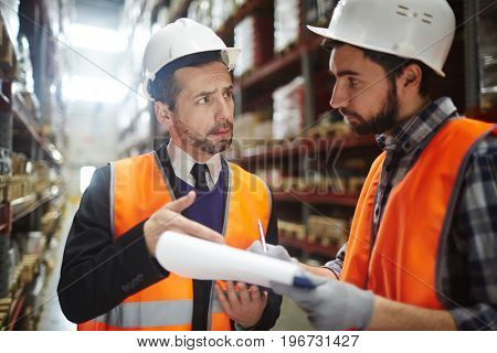 Portrait of warehouse worker talking to supervising manager while doing inventory control in entrepotTwo Warehouse Workers Reviewing Goods