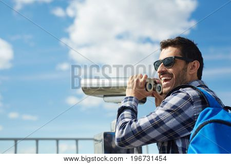 Portrait of young handsome man smiling happily while standing on rooftop against clear blue sky and using coin operated binoculars on viewing platform