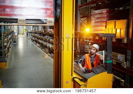 High angle portrait of warehouse worker using reach fork truck to load pallet with boxes on tall rack