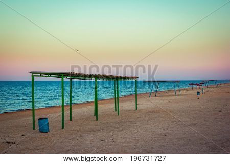 Abandoned beach at sunset. Sandy coast with old aged tents and umbrellas, blue wavy  water and colorful sky.