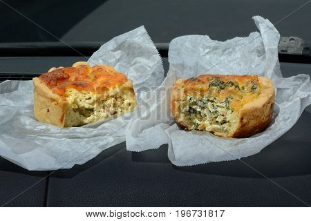 Breakfast for two on the go of two quiches, one sausage an green pepper and the other spinach and feta cheese on bakery paper on dashboard of automobile