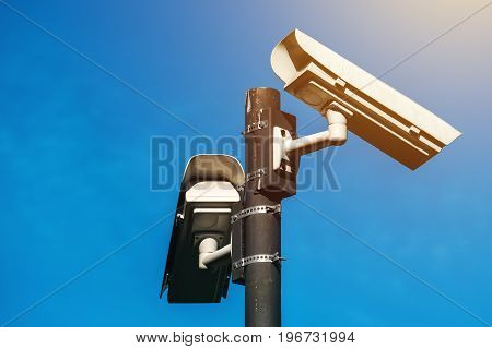 CCTV camera modern era anti-terrorist electronic surveillance security cameras against blue sky that symbolizes freedom