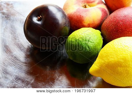 Fresh ripe organic fruits on vintage metal plate background.Lemon,lime,plum,mango and peaches.Diet,healthy food,raw food concept.Selective focus.
