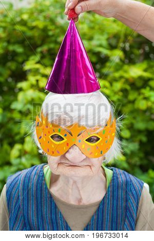 Portrait of a happy elderly woman celebrating birthday outdoor wearing a colorful hat and mask