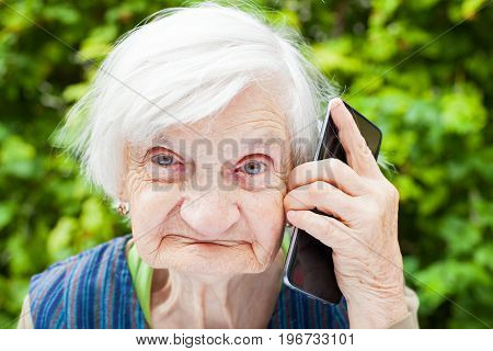 Picture of a happy smiling grandmother talking on a mobile phone outdoor in the garden
