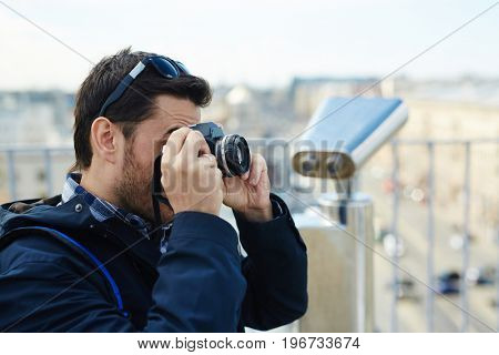 Young man taking picture using photo camera while standing on rooftop viewing platform against panoramic city view and coin-operated binoculars in background