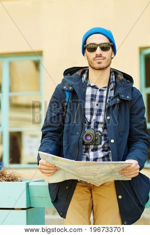 Portrait of modern young man  looking at camera holding map while  traveling alone in streets of old city