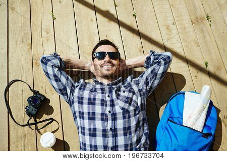 Top view portrait of handsome young man lying on wooden dock planks enjoying sunlight on tourist trip with photo camera and backpack nearby