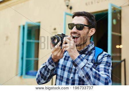 Portrait of handsome young man taking photos in streets of old city enjoying tourist trip in Europe