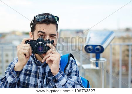Portrait of handsome young man taking picture with vintage photo camera
