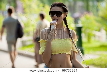Ice cream girl eating cone ice cream in park summer vacation smiling happy and cute at camera. Caucasian young woman with pigtails.