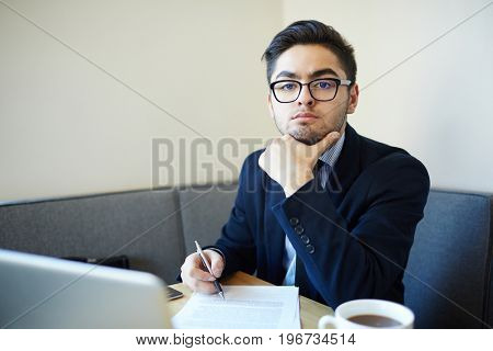 Serious specialist sitting by workplace in office