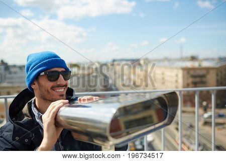 Portrait of young solo tourist smiling while enjoying panoramic view of city from rooftop platform using coin-operated binoculars