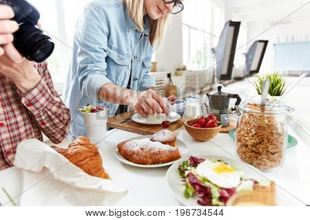 Food stylist preparing table with meals for photographing
