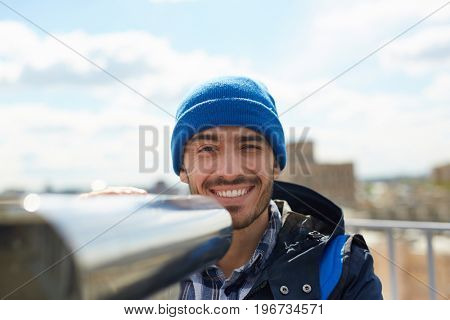Portrait of young solo tourist smiling looking at camera while enjoying panoramic view of city from rooftop platform using coin-operated binoculars