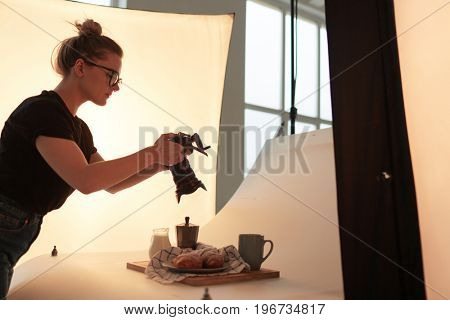 Young woman with photocamera shooting snack in studio
