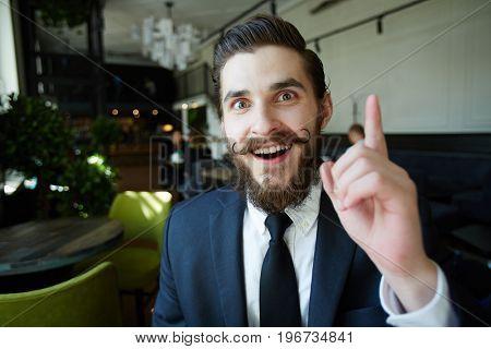 Inspired businessman pointing forefinger up