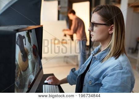 Serious food designer looking through shots in monitor