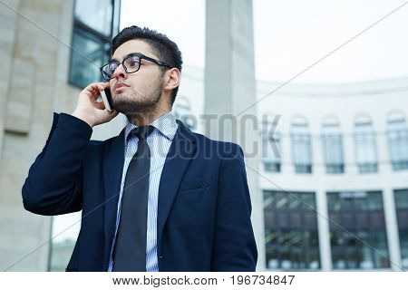 Serious agent speaking to client on smartphone