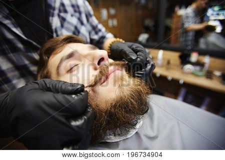 Barber taking care of client beard and moustache