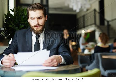 Banker in suit reading financial papers in cafe
