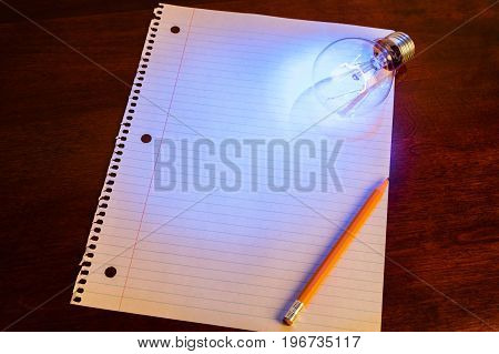 notebook paper and light bulb business education concept.