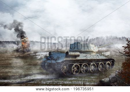 Soviet Tank goes through the swamp in the background of a burning tank. Tank battle on the battlefield