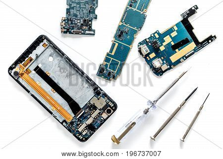 Parts of disassembled cell phone on white background top view.