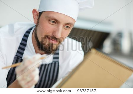 Chef writing recipe or menu of the day