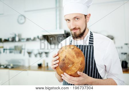 Baker in uniform, holding round loaf of crusty bread