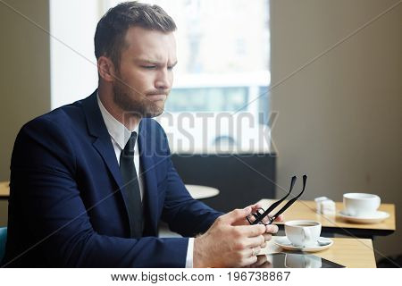 Young pensive businessman sitting by table in cafe