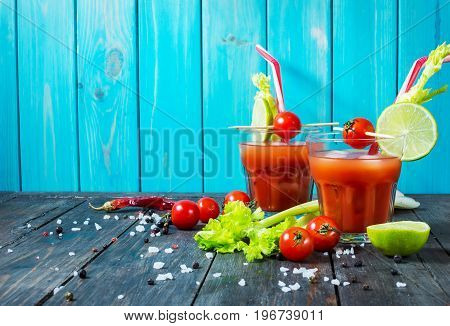 Cocktail Bloody Mary with ice in glasses on a wooden table. Copyspace