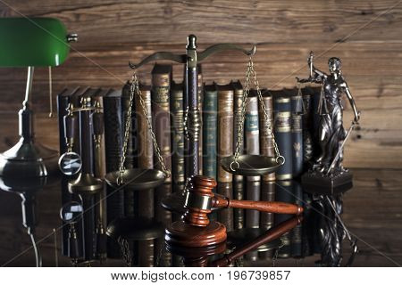 Gavel of the jugde and scale of justice in the court library. Wooden desk.