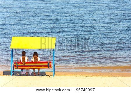 Romantic couple sitting on a swing on the beach. Two girls in love