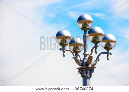 Beautiful street lamp on a background of blue, little cloudy sky