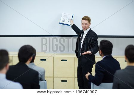 Trader with financial document pointing at whiteboard while presenting his points