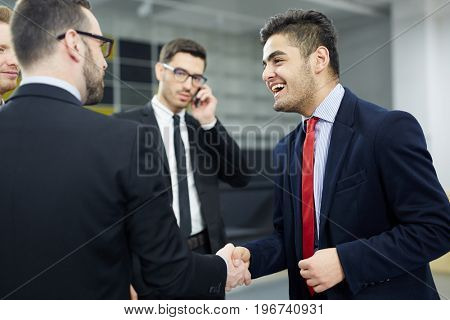 Happy businessman greeting his colleague by handshake