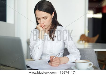 Businesswoman thinking of idea while reading paper