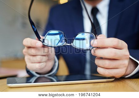 Human hands holding eyeglasses over touchpad