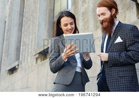 Young brokers reading online data outdoors
